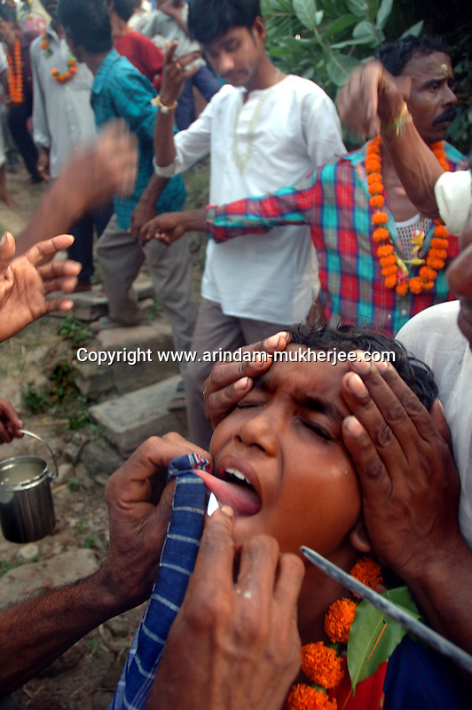 On the eve of Bengali new year a young boy piercing his tounge to bring good fate in the new yearwhile viewers watch the cerimoney. This is a sacrifice to Lord Siva done by people staying in the rural Bengal. Another form of religious blindness in one of the fastest developing country. Medinipore near Kolkata, India. Arindam Mukherjee.