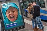 Nederland, Utrecht, 12-12-2012 -  Verliefd stel staat te zoenen naast een billboard van Natuurmonumenten met de tekst Ik wil Oerrr. FOTO: Gerard Til   / Hollandse Hoogte