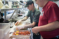 NWA Democrat-Gazette/CHARLIE KAIJO Rodney Snoxhill of Rogers (center) and Boar's Nest owner John Hudec (right) prepare a crawfish plate, Sunday, April 15, 2018 at the Boar's Nest in Rogers.<br />