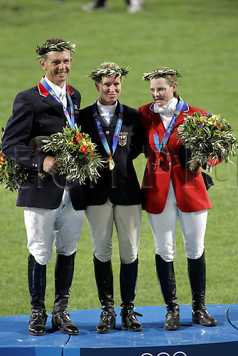 18 August 2004: British rider Leslie Law (GBR) silver, Bettina Hoy (GER) gold and Kimberly Severson (USA) bronze celebrate winning the Individual Eventing medals on the podium after the Eventing Showjumping Final held at the Markopoulo Olympic Equestrian Centre. Following a decision by the Court of Arbitration for Sport Bettina Hoy was handed 12 penalties for crossing the start line twice during her 1st round. This promoted Law to gold, Severson to silver and Funnell to bronze, Hoy moved to 9th overall after the dicision. 2004 Olympic Games, Athens, Greece. Photo: Neil Tingle/Action Plus..040818 olympics olympic showjumping horse horses showjumper showjumpers equestrian sport sports jumping jumper jumps show three-day event three day events 3-day 3 day eventing eventer eventers celebrations celebration celebrates celebrate joy celebrating