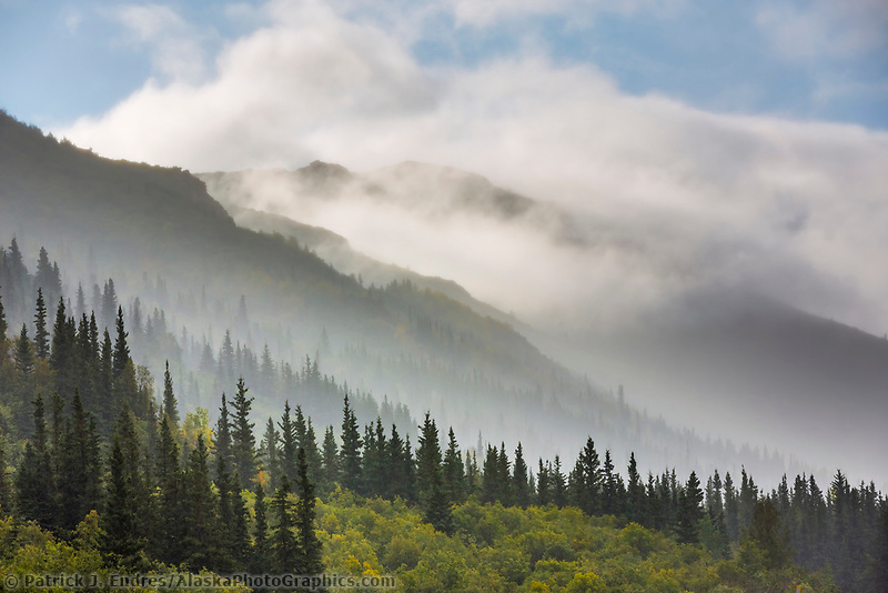 Mist and rain diffuse the layered mountains of the Alaska Range at the entrance to Denali National Park, Alaska