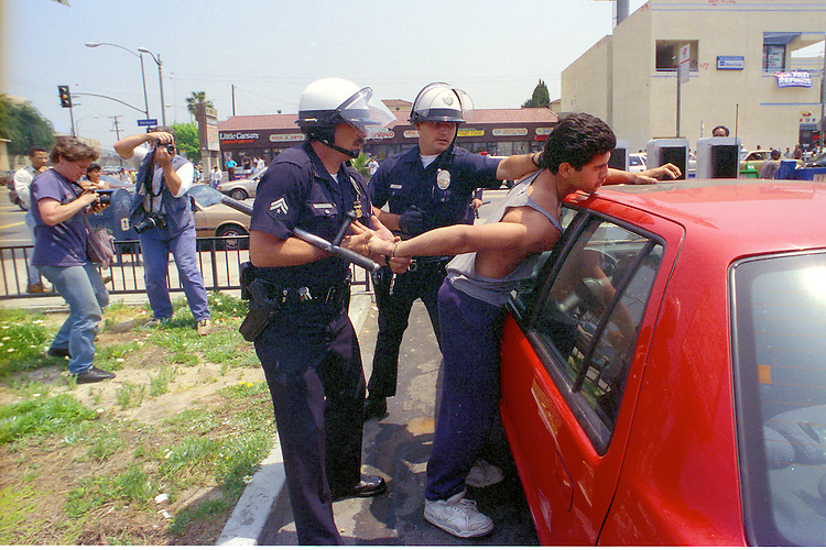 "Police take a suspected looter into custody during the ""uprising"" of rioting and looting in the Koreatown neighborhood of Los Angeles, Calif. following the acquittal of LAPD officers accused of beating motorist Rodney King, May 30, 1992. Photo copyright Gerard Burkhart 818-207-0273)during the ""uprising"" of rioting and looting in the Koreatown neighborhood of Los Angeles, Calif. following the acquittal of LAPD officers accused of beating motorist Rodney King, May 30, 1992. Los Angeles suffered city wide chaos and destruction following the the end of the first trial against accused officers Sergeant Stacey Koon, Laurance Powell, Theodore Briseno and Timothy Wind. A later  Federal Civil Rights Trial sent officers Powell and Koon to prison for 30 months while Briseno and Wind were acquitted. Photo copyright Gerard Burkhart 818-207-0273)"