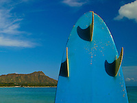 A surboard stands ready for the big waves with Diamond Head in background. Photo taken near Ala Moana Beach park, Oahu.