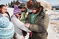 Ray Redington Jr. autographs a young girl's shirt at the village of Koyuk in Arctic Alaska during the 2010 Iditarod