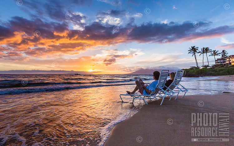 A vacationing couple watch the sunset and relax in lounge chairs that are nearly in the surf at a beach in Wailea, Maui.