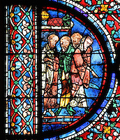 Four apostles to the left of the scene of 2 thurifers or incense-bearer angels swinging censers, pointing down to the funeral procession of Mary, from the Glorification of the Virgin stained glass window, in the nave of Chartres Cathedral, Eure-et-Loir, France. This window depicts the end of the Virgin's life on earth, her dormition and assumption, as told in the apocryphal text the Golden Legend of 1260. Chartres cathedral was built 1194-1250 and is a fine example of Gothic architecture. Most of its windows date from 1205-40 although a few earlier 12th century examples are also intact. It was declared a UNESCO World Heritage Site in 1979. Picture by Manuel Cohen
