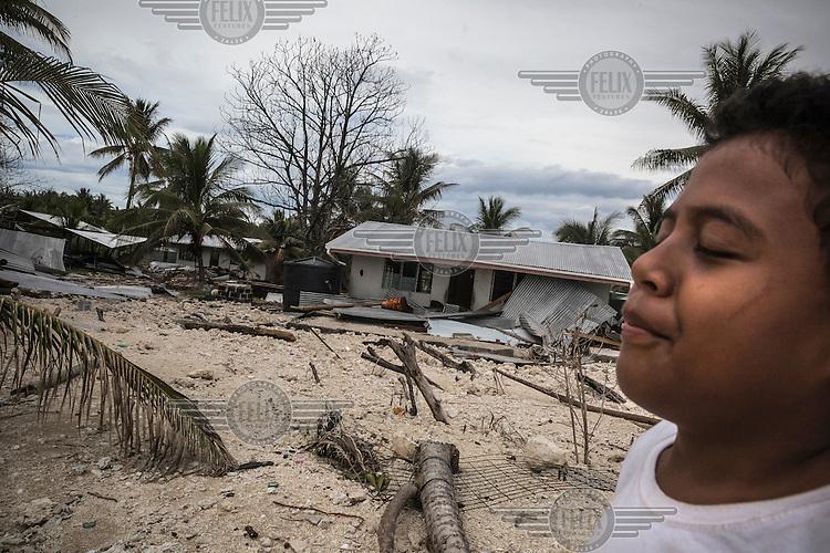 A child standing in front of a damaged house on the Nui Atoll. Nui was affected by storm surges caused by Cyclone Pam in which 12 houses were completely destroyed and 110 homes badly damaged. 71 families (40% of the population) from Nui were displaced and were living in evacuation centres or with other families. According to Tuvalu Prime Minister Enele Sopoaga estimated 45 percent of the nation's nearly 10,000 people were displaced.