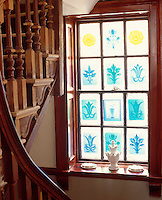 Resin casts of architectural mouldings by artist Peter Hone create a stained-glass effect on the landing