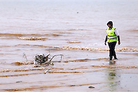A volunteer collects loose debris from the beach in Nea Mihaniona