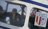 Saturday, Feb. 18, 2006  Anchorage, Alaska. Volunteer Iditarod Airforce pilot Reagan Russey loads straw into his Cessna plane prior to flying them  out to checkpoints along the trail.  Each musher is given one bale of straw at a checkpoint to bed their dogs down.