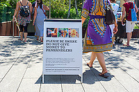 A sign on the High Line Park in New York on Saturday, July 23, 2016 warns visitors not to give money to panhandlers dressed as monks. (© Richard B. Levine)
