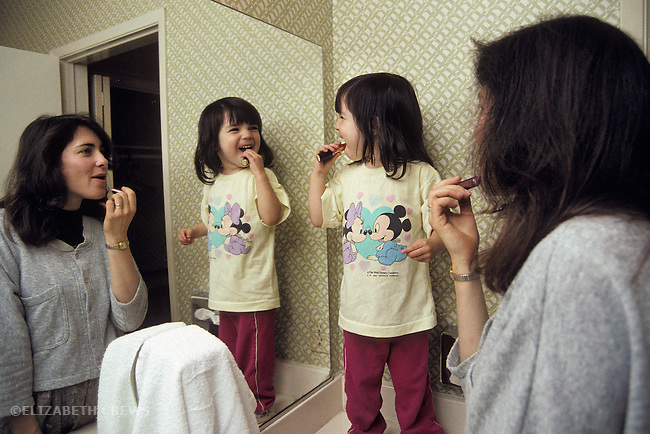 San Diego CA Girl, two-years-old, imitating mother putting on makeup at home