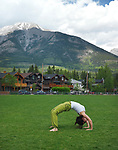 Young woman practicing yoga, doing bridge exercise outdoors in Centennial Park in Canmore, town in Alberta's Rockies with Rocky mountains in the background. Canmore, Alberta, Canada. 2017