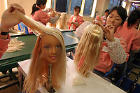 CAN0 20040226 GUANYAO, CHINA : Chinese workers that work at the 'Barbie' division shown assembling the 'Cool Crimpin' Styling Head' Barbie at the Mattel (H.K.) Ltd. plant in Guanyao, China on Thursday 26 February, 2004. Mattel is the largest toy maker in the world, and manufactures various products from Barbie to Hot Wheels in China.