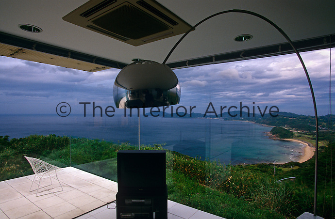 An Arco lamp frames the spectacular view through the glass walls of the living room
