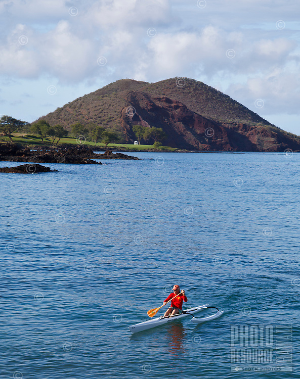 A man paddling a one-person outrigger canoe enjoys his surroundings off of Makena Landing, South Maui.