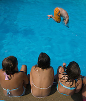 Girls watch as adults dive into pool