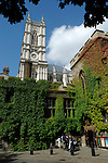 Westminster Abbey tower viewed above the colourful ivy walls of Dean's Yard cloister, London