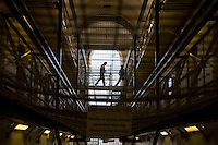 A prison officer escorts an inmate to his cell. HMP Wandsworth, London, United Kingdom.