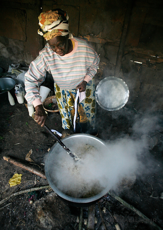 A woman cooks a pot of rice for the Rurii Women's Group before lunch in Kibiko, Kenya.