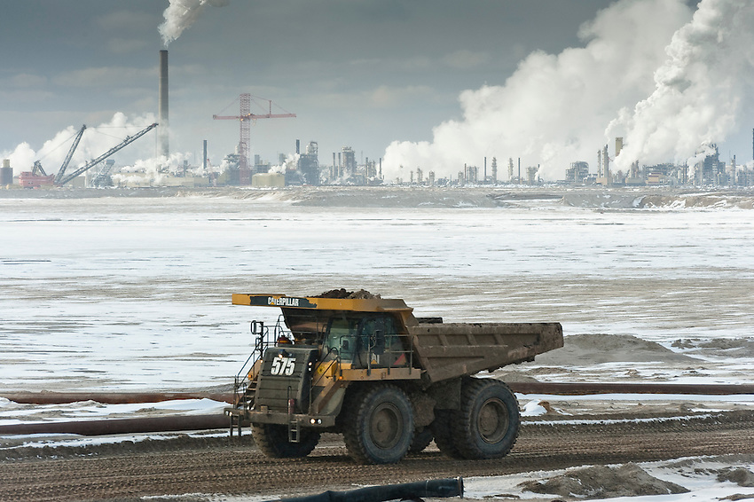 Syncrude Truck and Upgrader. Alberta Tar Sands, Northern Alberta, 2010. Behind a large truck and across a partially frozen tailings pond lies Syncrude's Mildred Lake upgrader. The Tar sands are Canada's single largest, and fastest growing source of carbon. This carbon footprint is a primary reason why Canada, who was one of the original signatories of the Kyoto Protocol, has walked away from this agreement.  Alberta Tar Sands, Northern Alberta, Canada.  Nikon D3, 70-200mm f2.8 shot at 200mm, f8, 1/200th, at ISO 400.
