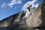 Ash cloud and debris flow from explosive strombolian eruption rising from active crater of Batu Tara Volcano, Komba Island, Indonesia.