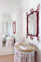 Detail of a bathroom with a sink draped in sheer white and red fabric, a coral inspired mirror hangs above