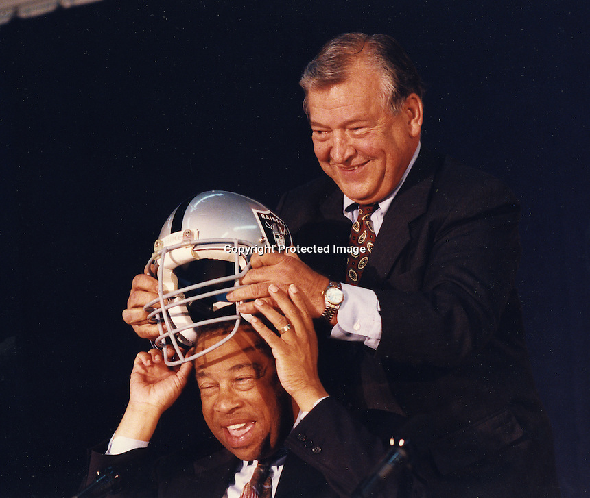Oakland California, Aug 1995: George Vukasin puts Oakland Raider helmet on Oakland mayor Elihu Harris.<br />