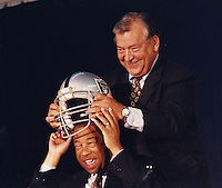 Oakland California, Aug 1995: George Vukasin puts Oakland Raider helmet on Oakland mayor Elihu Harris.<br />occasion of the Raiders return to Oakland from Los Angeles. (photo 1995 by Ron Riesterer)