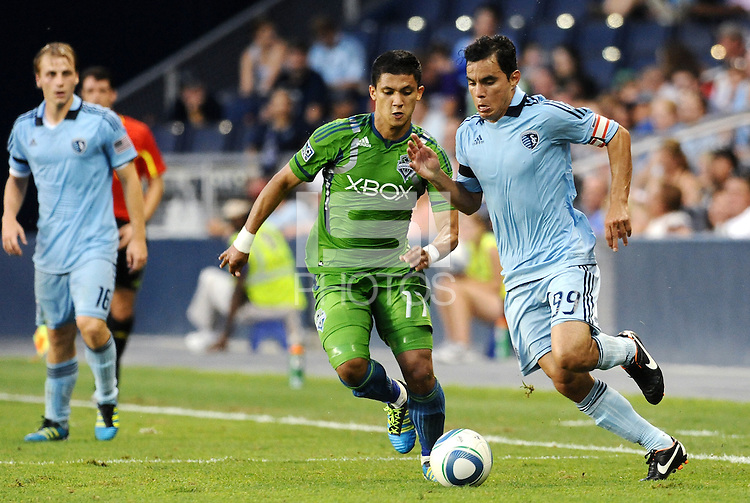 Omar Bravo (99) midfielder Sporting KC  moves past Fredy Montero (17) ) forward Seattle Sounders... Sporting Kansas City were defeated 1-2 by Seattle Sounders at LIVESTRONG Sporting Park, Kansas City, Kansas.