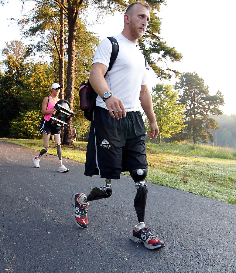 Former Marine sergeant Rob Jones, right, walks with partner Oksana Masters on their way to the boat dock to train Wednesday July, 25, 2012 on the Rivanna River in Charlottesville, VA. Former Marine sergeant Jones, who lost both legs during an IED explosion in Afghanistan, will compete with Masters as rowers at the 2012 Paralympics in London, England. Rowing will make its appearance at the London Paralympic Games for only the second time, after its introduction at the Beijing 2008 Games. Photo/Andrew Shurtleff