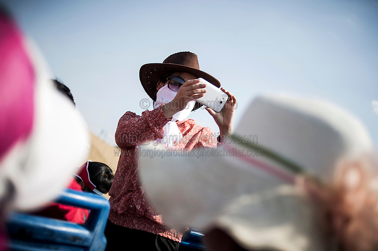 A Chinese tourist takes a picture on a shuttle bus as she wears scarf and hat to protect from the sun of the Gobi Desert in Inner Mongolia, China, July 27, 2014. <br /> <br /> Smartphones are an essential tool of Chinese ordinary life. Everywhere in China, people use them to take pictures to share online, to talk and chat, to play videogames, to get access to the mainstream information, to get connected one each other. In the country where the main global social media are forbidden - Facebook, Twitter and Youtube are not available  -, local social networks such as WeChat have a wide spread all over the citizens. The effect is an ordinary and apparently compulsive way to get easy access to digital technology and modern way of communication. <br /> A life through the display. Yes, We Chat.<br /> <br /> © Giorgio Perottino