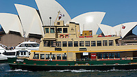 A ferry and a harbour cruise ship pass in front of Sydney Opera House.