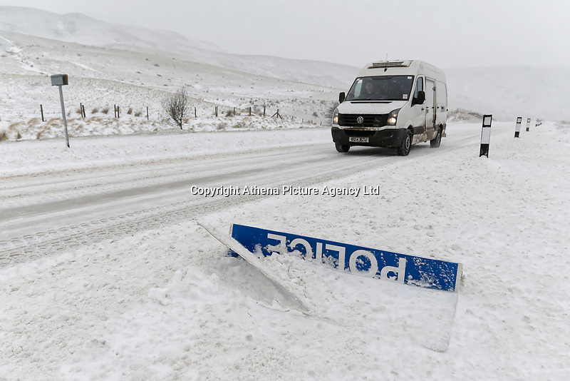 """WEATHER PICTURE WALES<br /> Pictured: A van drives past a """"Police Slow"""" sign covered by snow at the side of the A470 road in Storey Arms, Brecon Beacons in south Wales, UK. Friday 02 March 2018<br /> Re: Beast from the East and Storm Emma has been affecting most parts of the UK."""