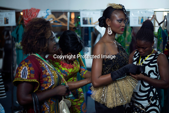 KINSHASA, DRC - JULY 25: A fashion model walking for the designer Moseka gets dressed backstage before a show at Kinshasa Fashion Week on July 25, 2015, at Shark club in Kinshasa, DRC. Local and invited foreign-based designers showed their collections during the second edition of Kinshasa Fashion week. Photo by Per-Anders Pettersson)