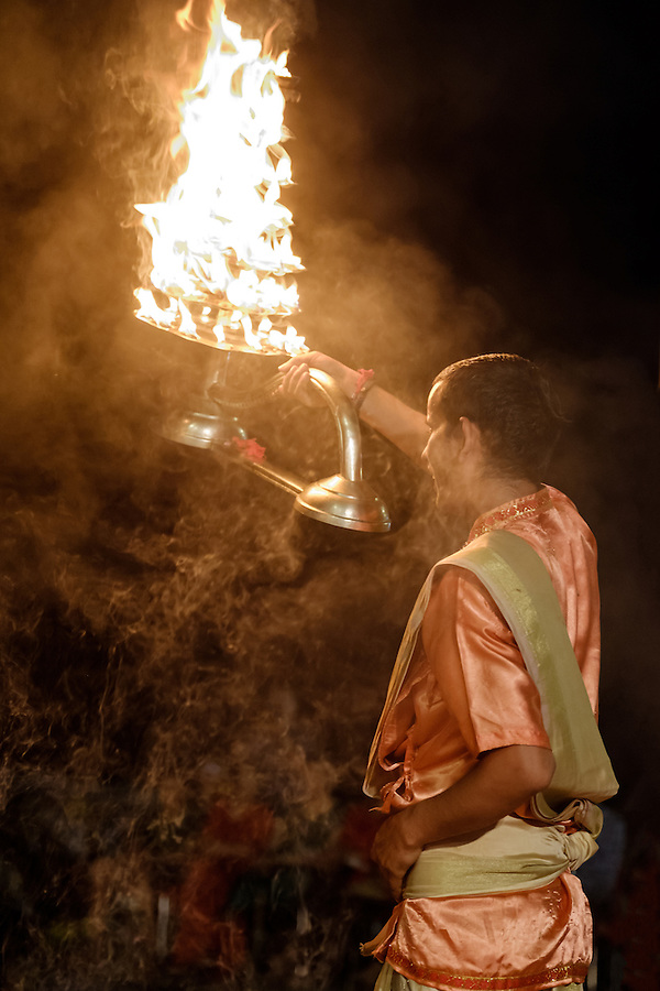 VARANASI, INDIA - CIRCA NOVEMBER 2016:  Young pandit performing the Ganga Aarti ceremony at the  Dasaswamedh Ghat in Varanasi. The Aarti is a powerful and uplifting spiritual ritual that takes place every evening at dusk. Varanasi is the spiritual capital of India, the holiest of the seven sacred cities and with that many rituals and offerings are performed daily by priests and hindus.