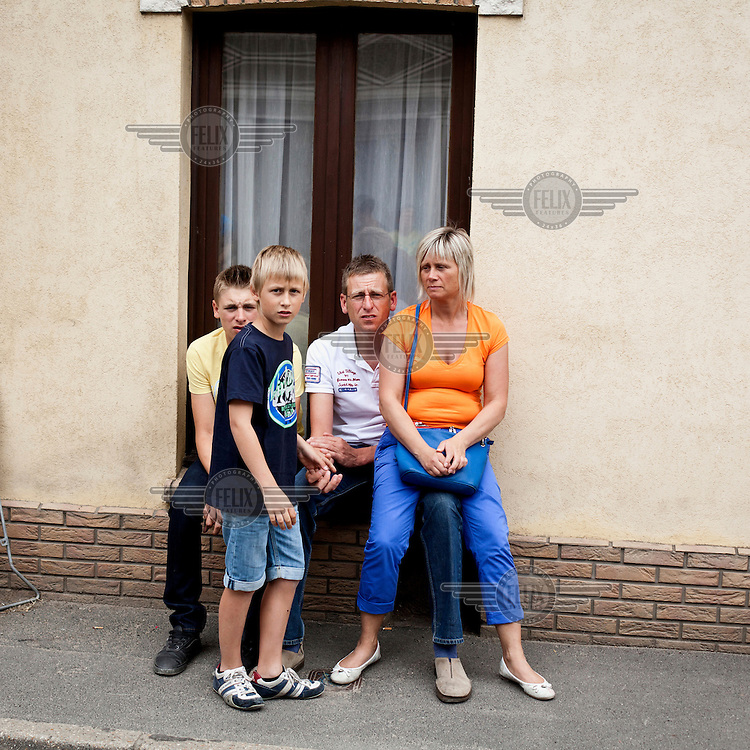A family wait beside a road for the riders of the Tour de France to pass by.