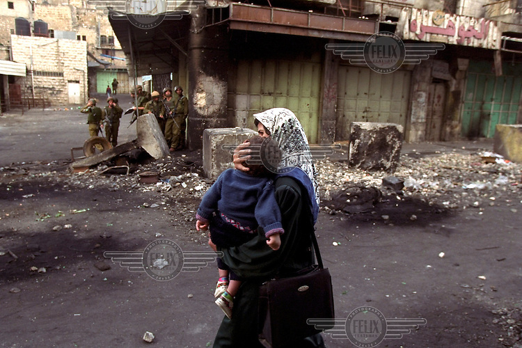 Mother with child. A woman hurries past Israeli soldiers as clashes erupt in the center of Hebron.