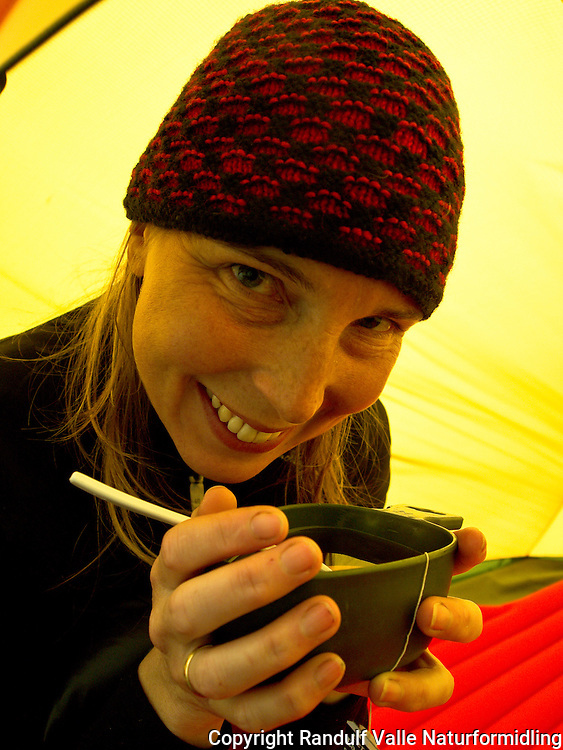 Dame drikker te i telt. ---- Woman drinking tea in tent.