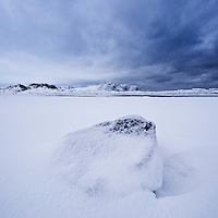 Rock in snow covered field, Vestvågøy, Lofoten islands, Norway
