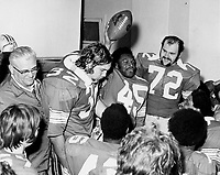All-American Archie Griffin , whose 45-yard final period touchdown run closed out Ohio State's scoring in the 42-21 Rose Bowl victory in 1974 against the USC Trojans, holds the game ball he was presented in the dressing room. Coach Woody Hayes is at left. Other Ohio State players are Rick Middleton (32) and Kurt Schumacher (72). Columbus Dispatch file photo