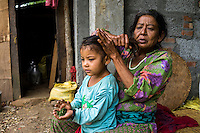 Aastha Baniya (6, in blue) allows her grandmother Bhagawati Baniya (56) to prepare her for school in their temporary home in Chautara, Sindhupalchowk, Nepal on 29 June 2015. The three girls lost their mother during the April 25th earthquake that completely levelled their house. Aastha was buried under the rubble together with her mother but Aastha survived. As their father Ratna Baniya (28) cannot care for the children on his own, SOS Childrens Villages has since been supporting the grandmother with financial and social support so that she can manage to raise the children comfortably and ensure that they will all be schooled. Photo by Suzanne Lee for SOS Children's Villages