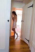 Woman wearing negligee standing in hallway