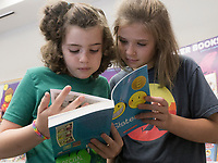 NWA Democrat-Gazette/CHARLIE KAIJO Liliana Yingst, 9 and Eden Yingst, 13, (from left) of Centerton read during the Scholastic Book Fair, Thursday, June 6, 2019 at the 21c Hotel in Bentonville<br />