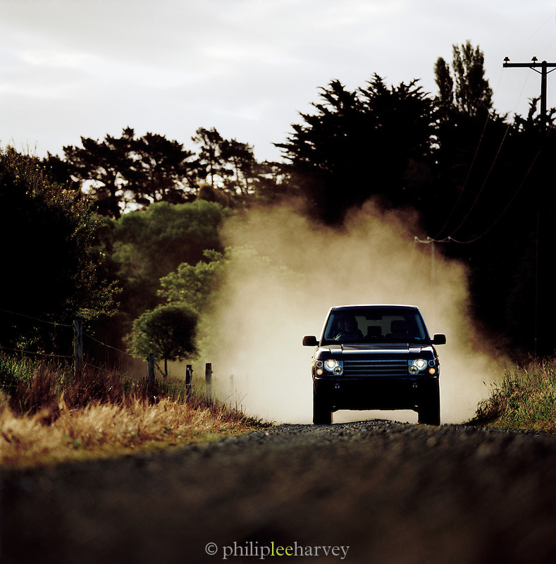 4x4 car driving down a dusty dirt track in the countryside of New Zealand