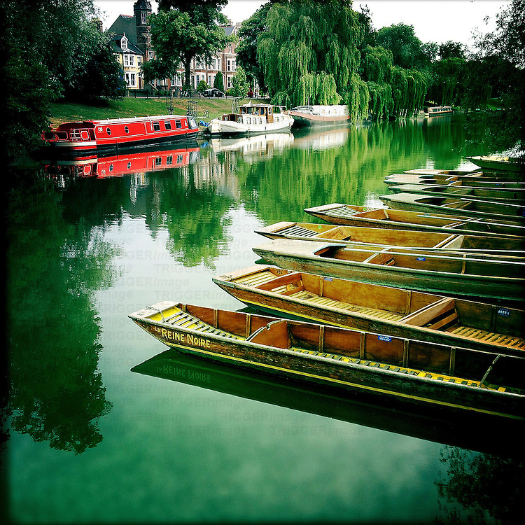 Punts and pleasure boats moored on river bank in Cambridge, Cambridgeshire, England with reflections in water