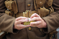 A mn in World War I gear rolls a cigarette outside Swansea Railway Station, south Wales UK. Friday 01 July 2016
