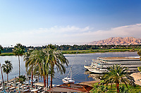 Nile River and docked sightseeing boats, and distant Valley of the Kings, from modern day Luxor or ancient Thebes, Egypt