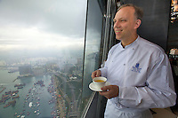 China, Hong Kong S.A.R..The Ritz-Carlton, Hong Kong. World's highest Dim Sum at Tin Lung Heen. Peter Find, Executive Chef, drinking tea and enjoying the view.