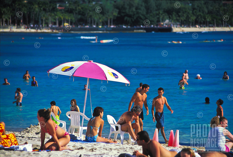 People on vacation love the sand, sun , and blue waters offered at Waikiki Beach.